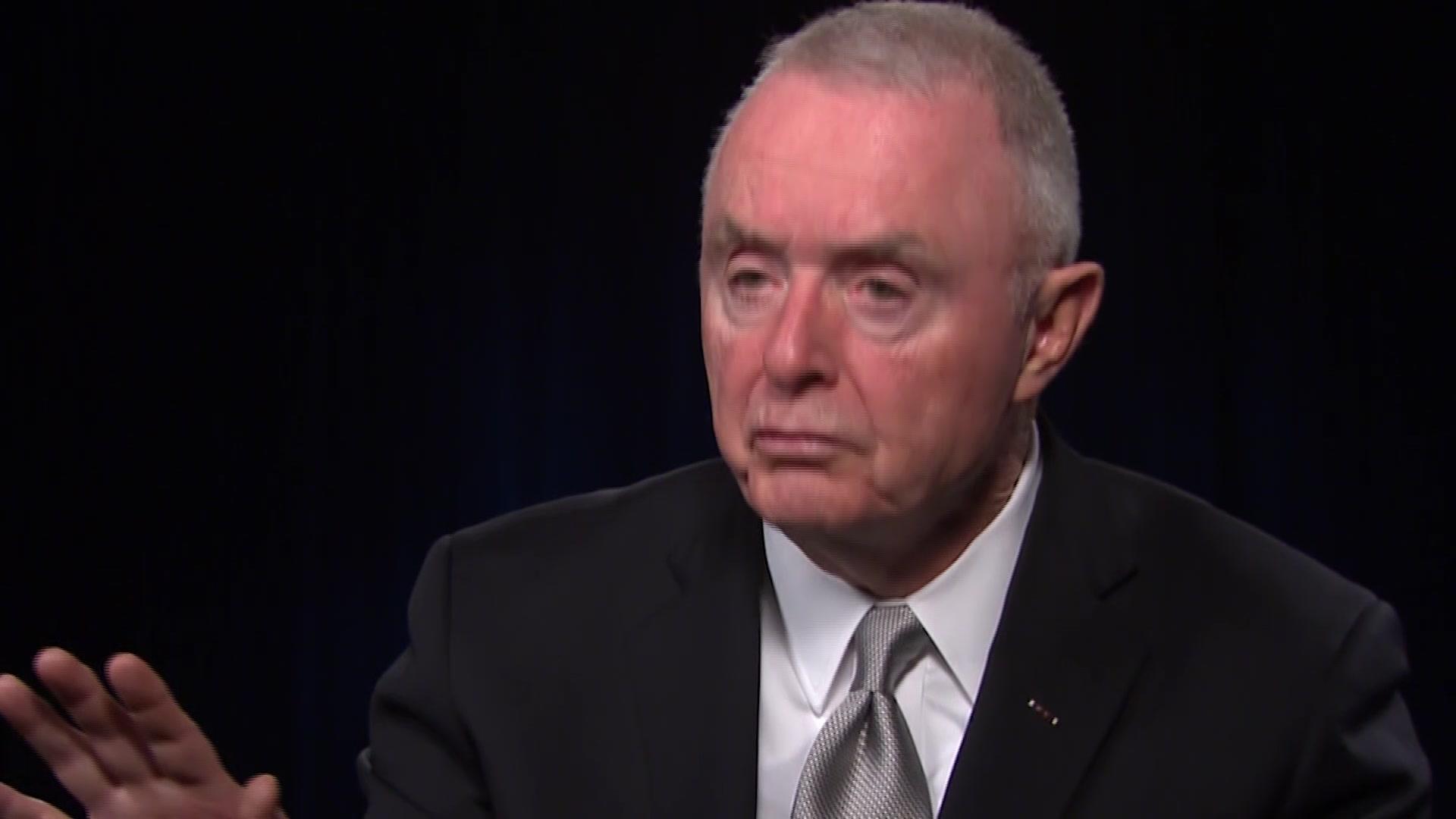 A civilian speaks against a dark background.