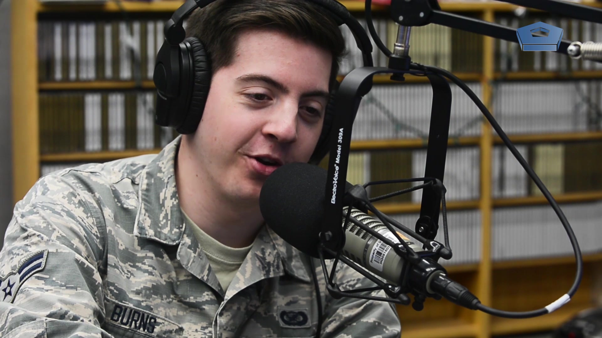 A service member speaks into a microphone from behind a radio station control board.