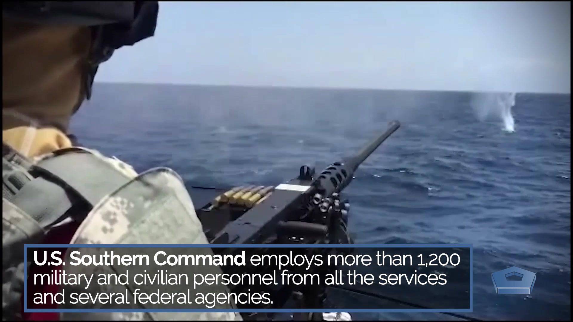 A service member fires rounds from a machine gun toward the ocean.