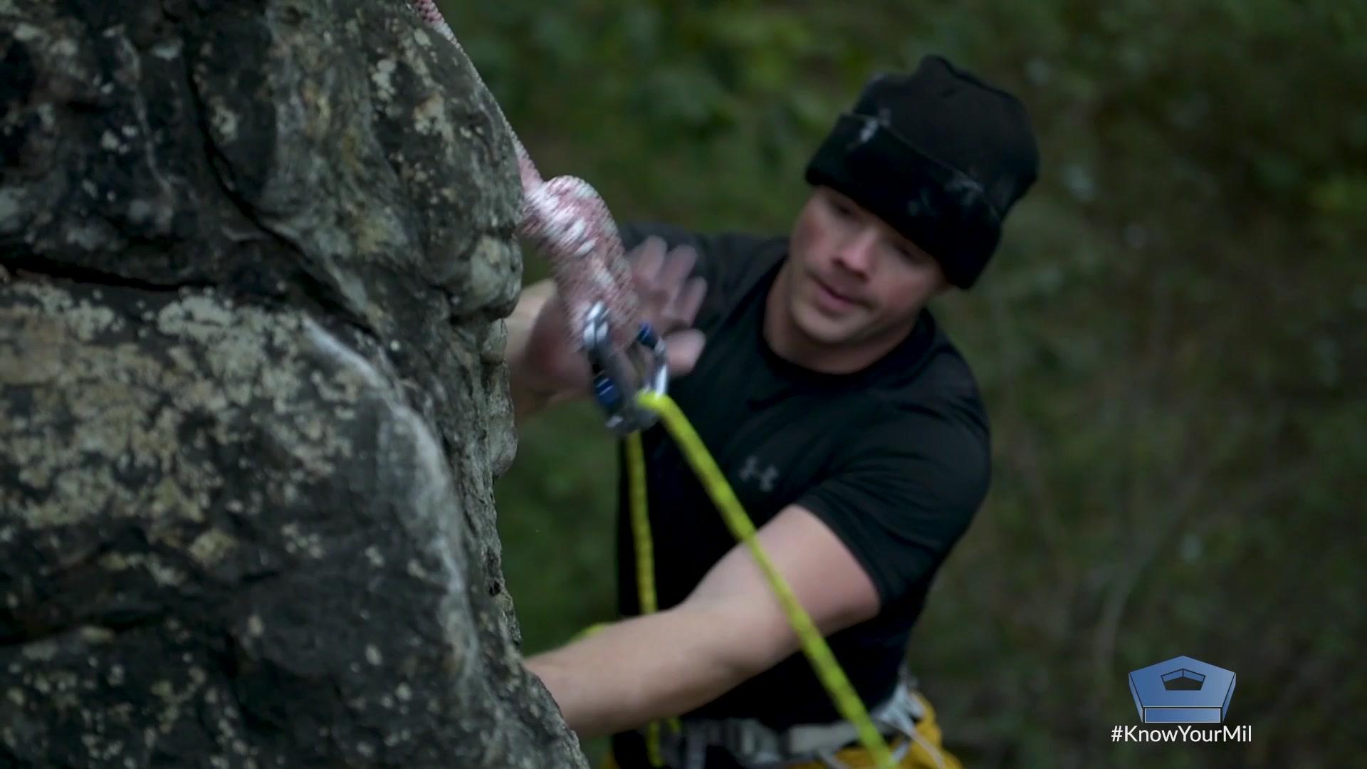 A service member rock climbs.
