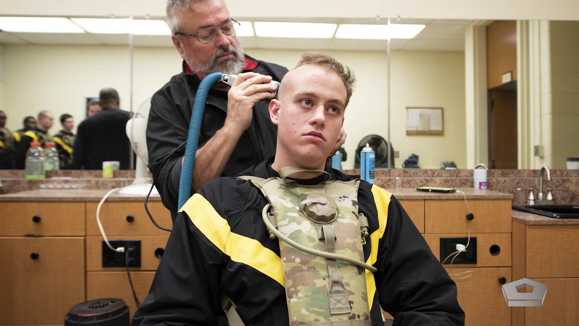 A barber shaves a new recruit's head with an electric razor as other recruits are seen in a mirror.
