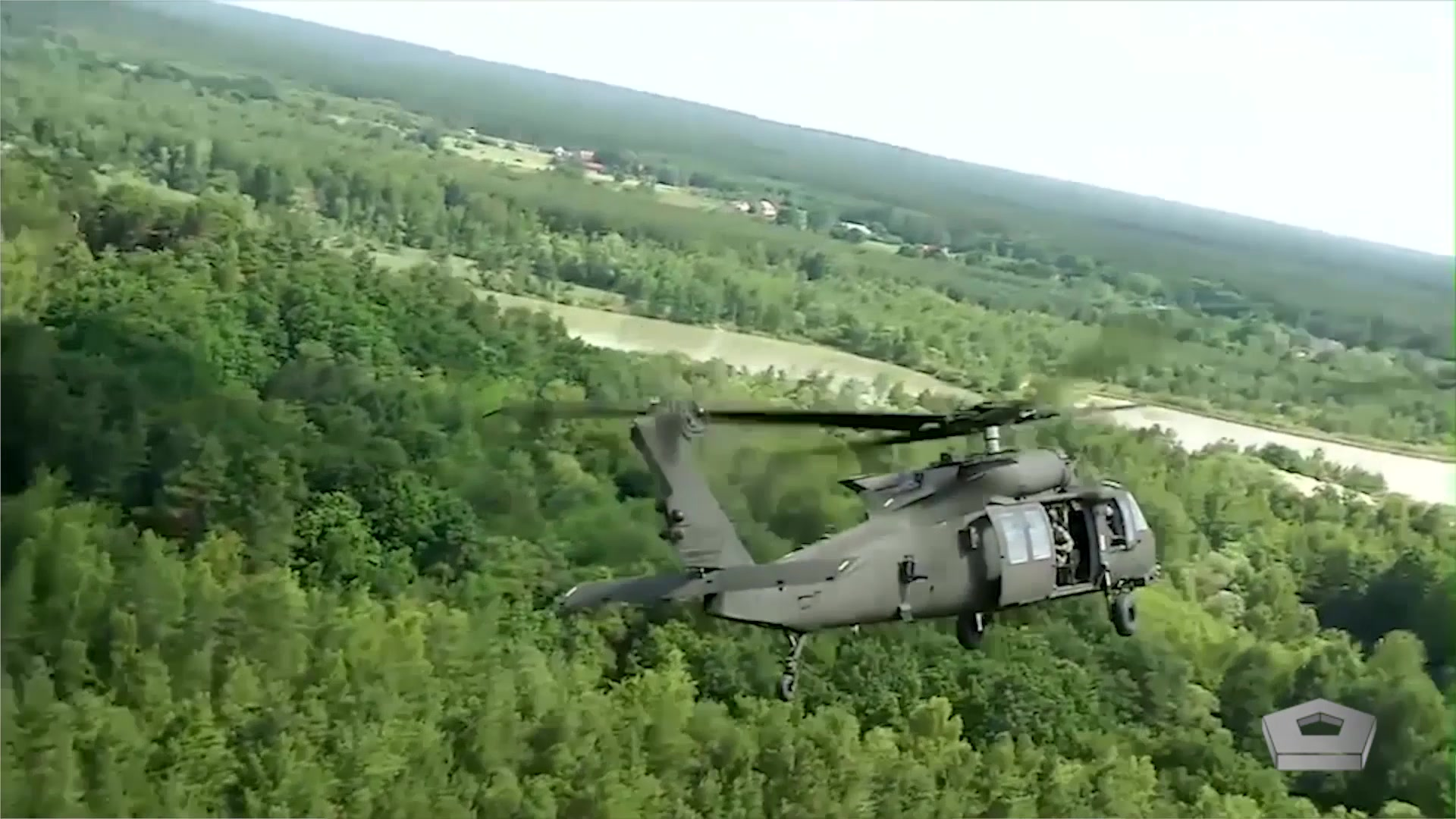 An Army helicopter flies over a forest.