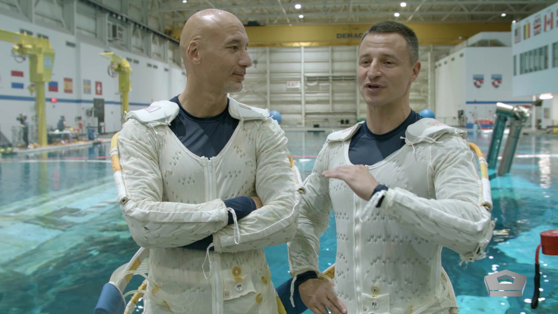Two astronauts stand in front of a pool.