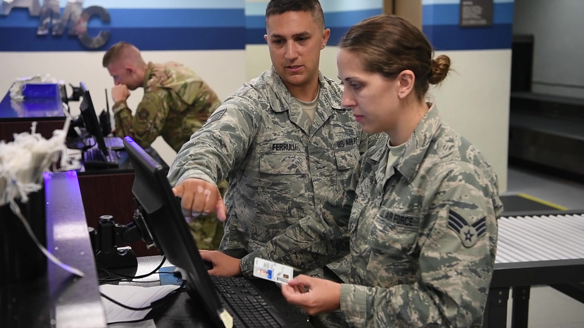 An Air Force Reservist works alongside active duty personnel to accomplish air transportation specialist responsibilities.