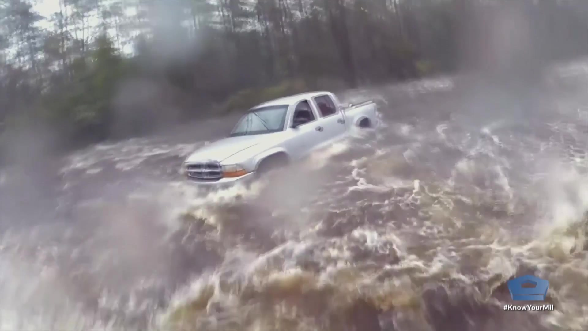 High, rushing water surrounds a white pickup truck.