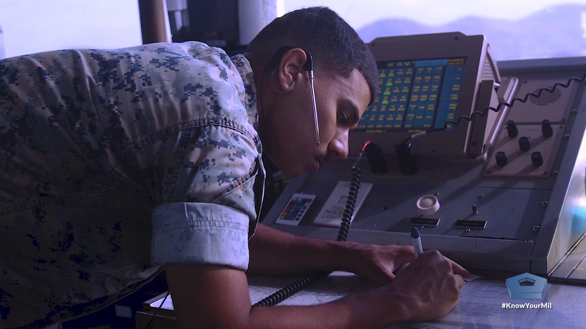 A Marine writes while in an air traffic control tower.