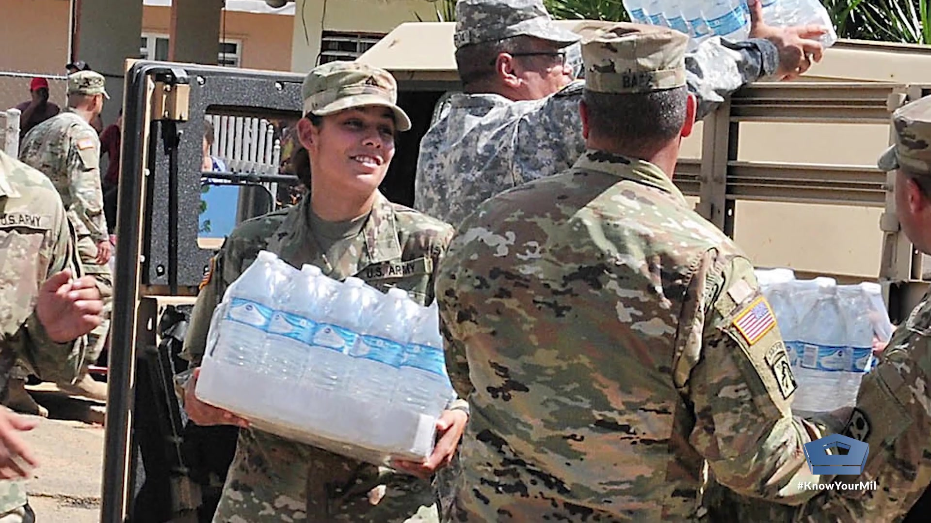 Service members help carry water.