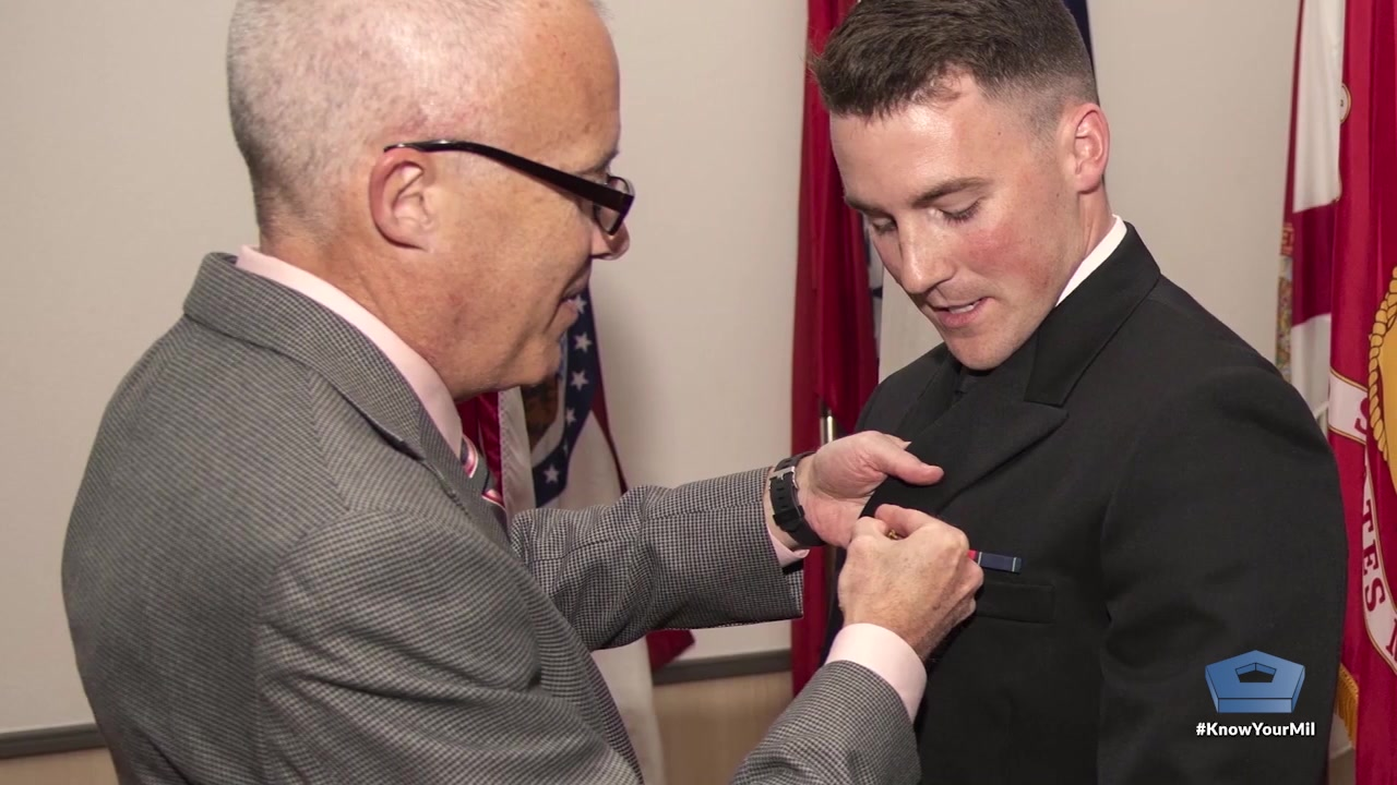 An man puts a pin on another man's jacket.
