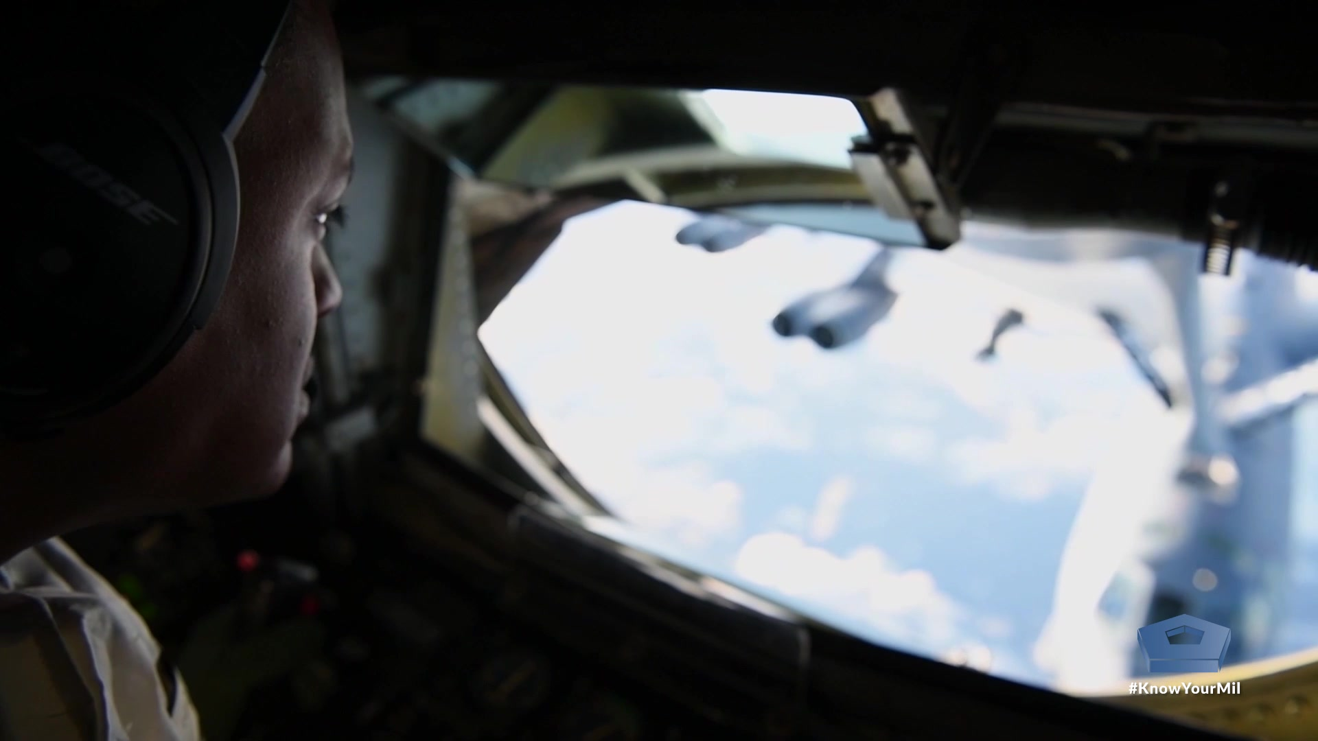 An airman looks out the window of an aircraft.