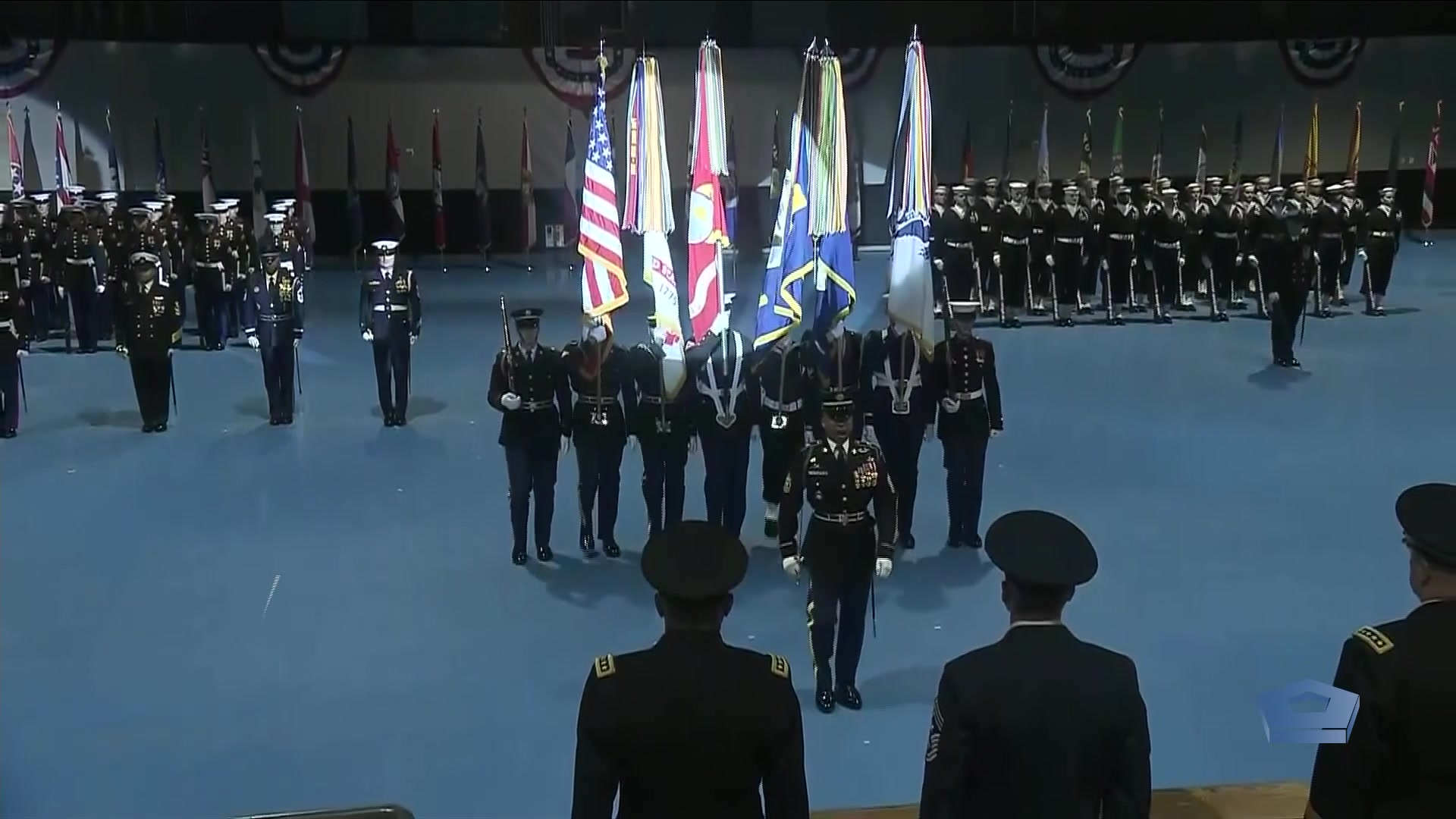 A group of service members stand in rows during a ceremony; some holding flags.