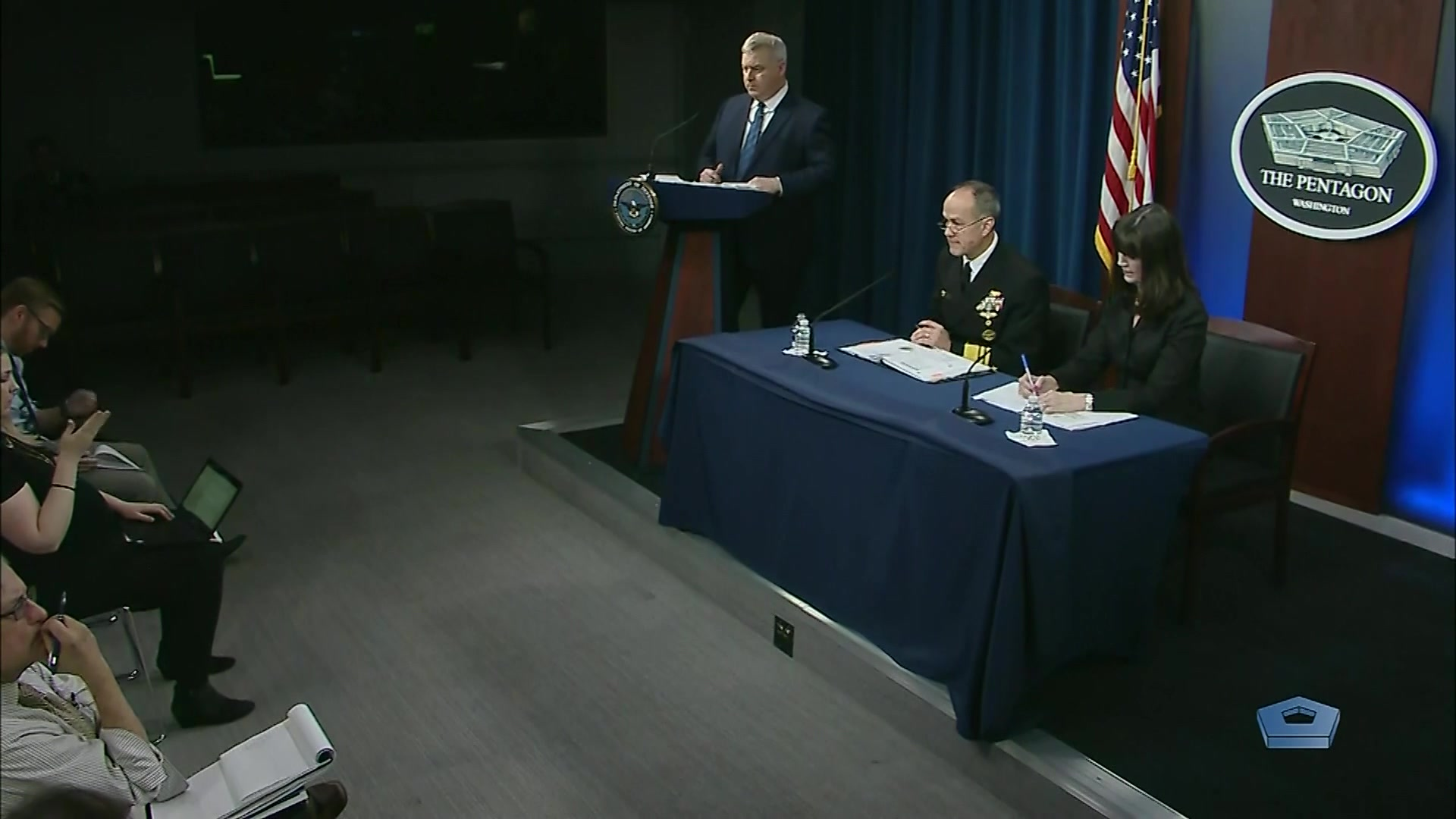 A sailor and civilian sit at a table in front of reporters, while another civilian stands at a lectern.