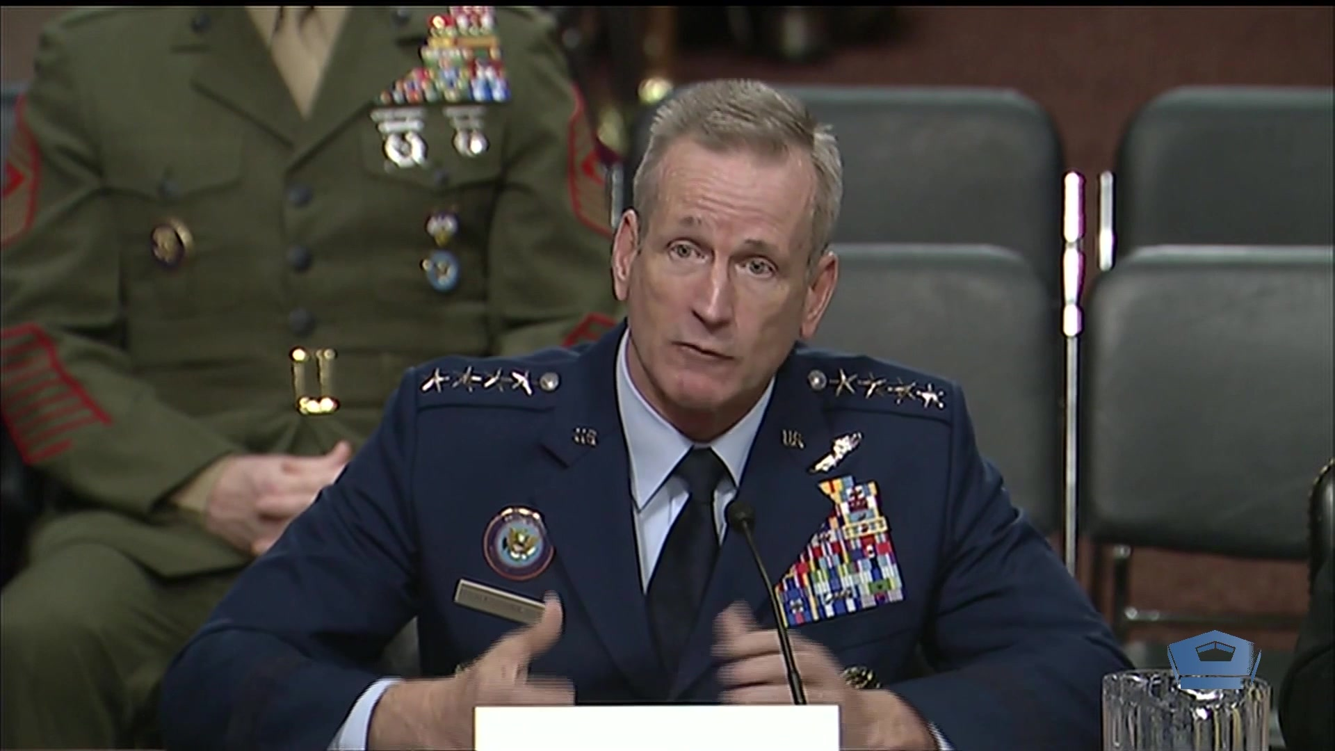 An Air Force general talks while seated in front of a microphone.