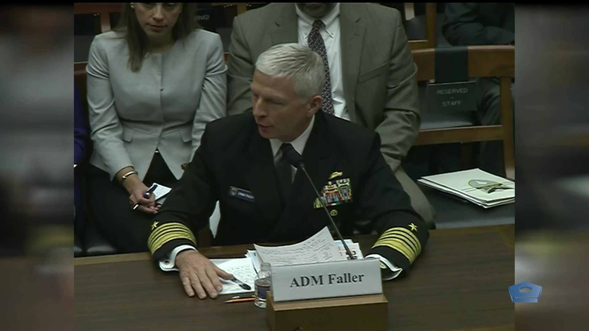 A Navy admiral sits at a table.