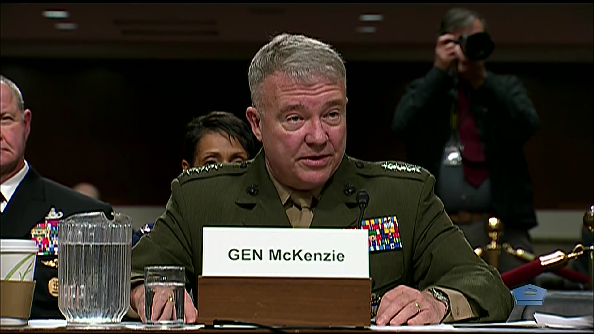 A Marine Corps general sits at a table.