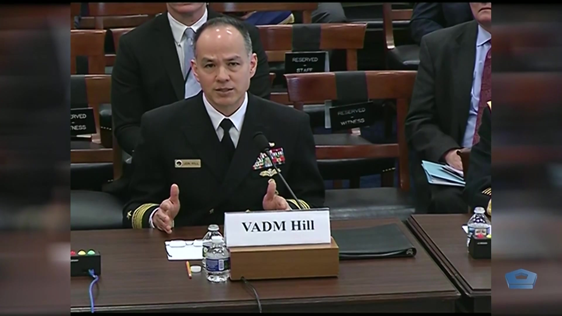 A Navy vice admiral speaks at a table.