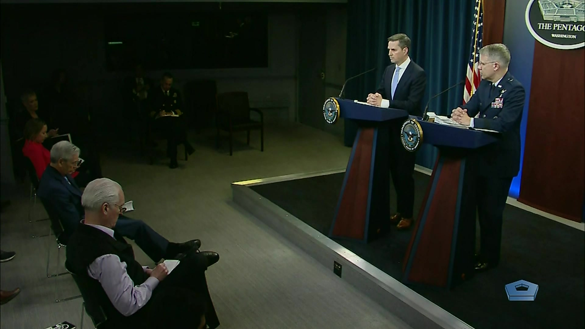 A civilian and an airman stand at lecterns in front of seated reporters.