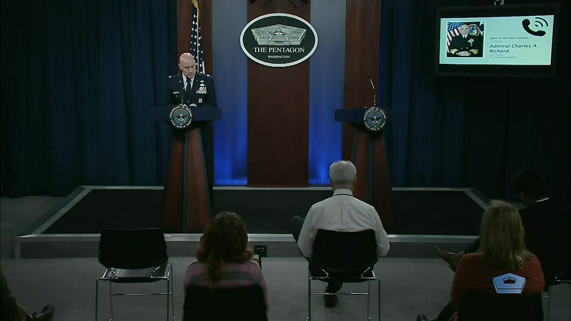 A service member stands at a lectern in a briefing room, as the photo of another one appears on an overhead screen.