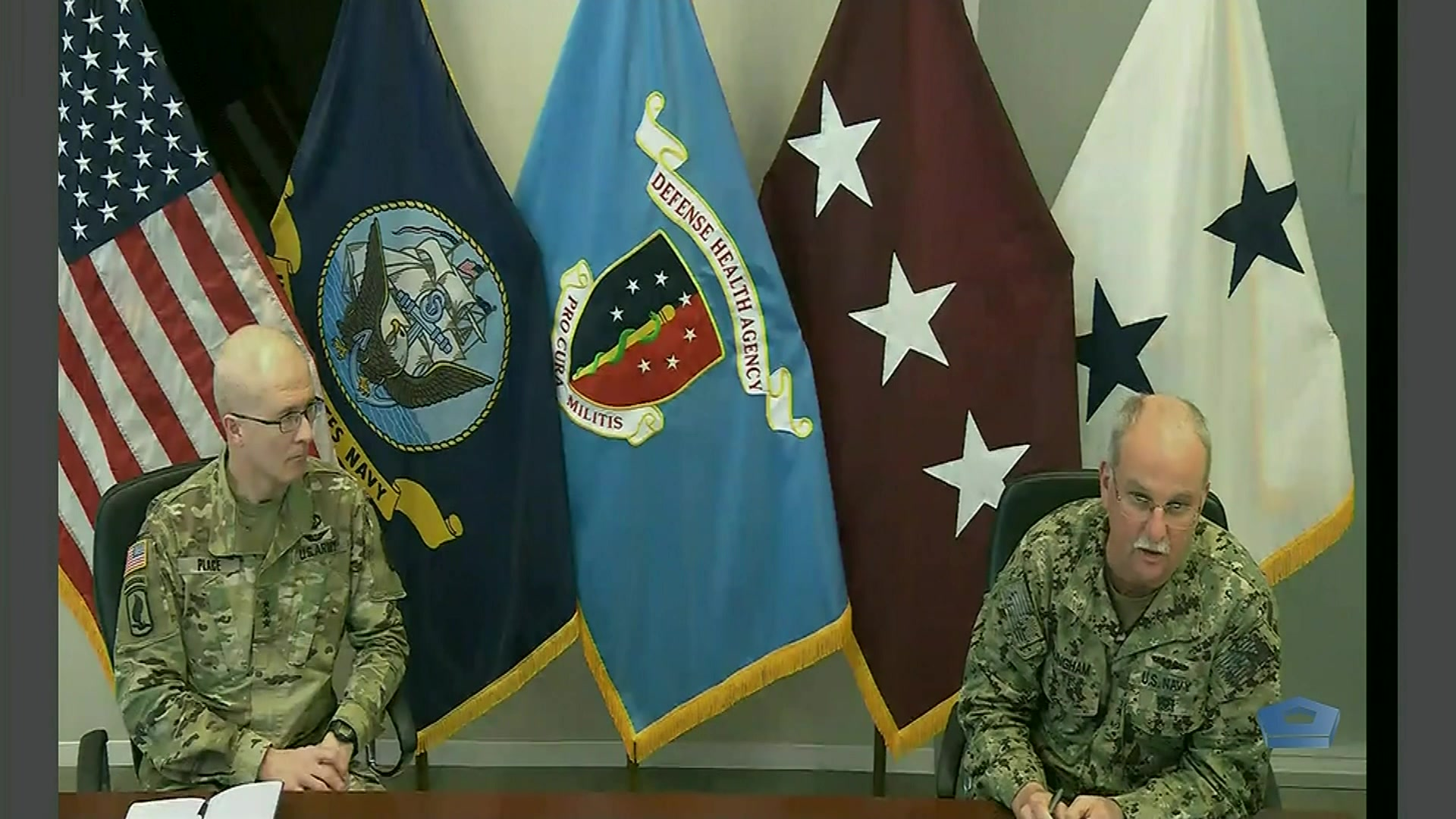 Two military officials sit and speak at a table in front of flags.