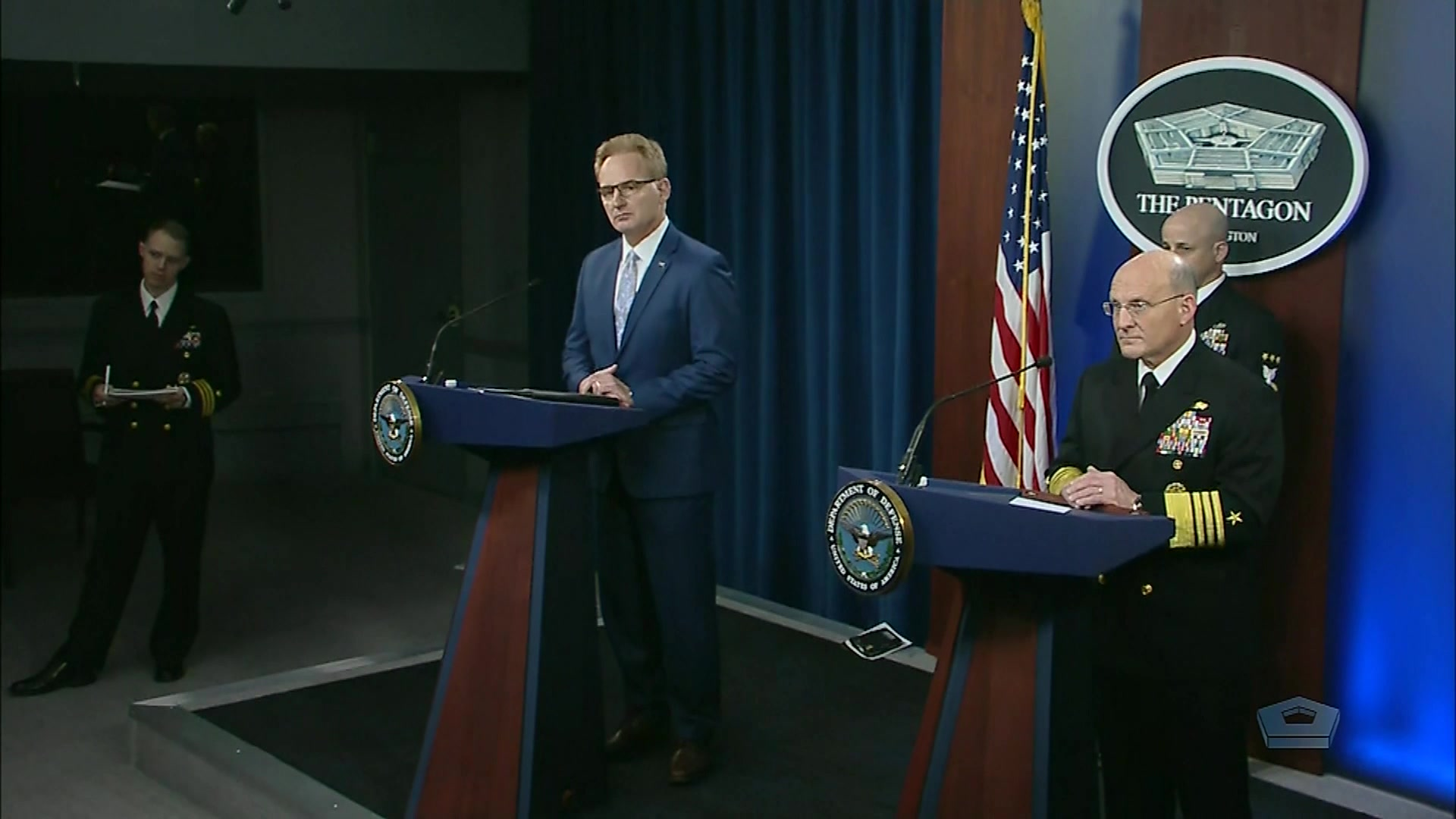 A civilian and a Navy admiral stand at twin lecterns.
