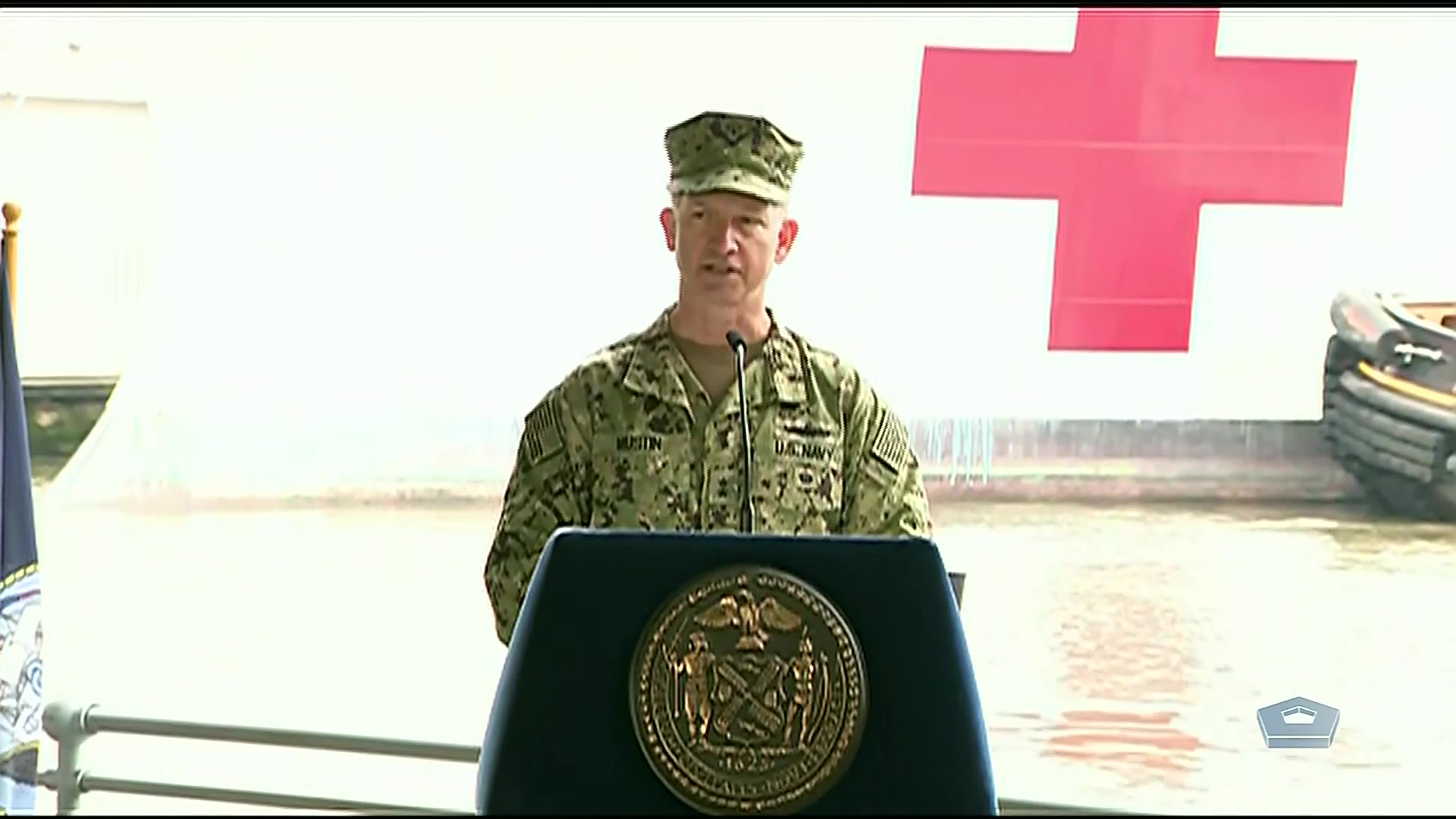 A sailor speaks at a lectern.