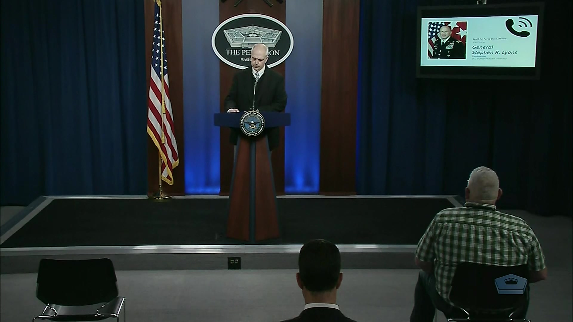 A civilian speaks at a lectern while an image of an Army general is on screen in the background.