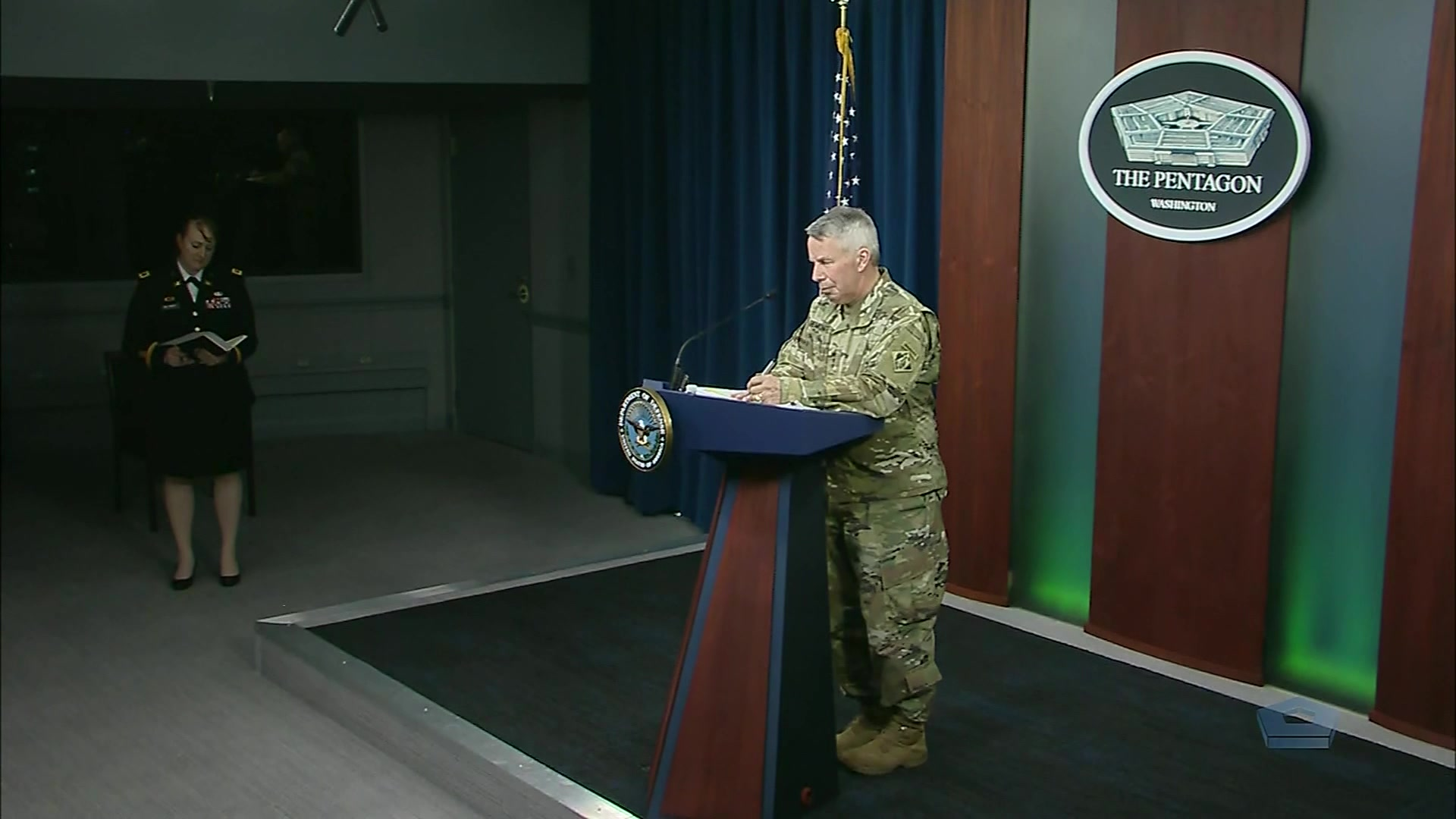 An Army general speaks at a lectern.