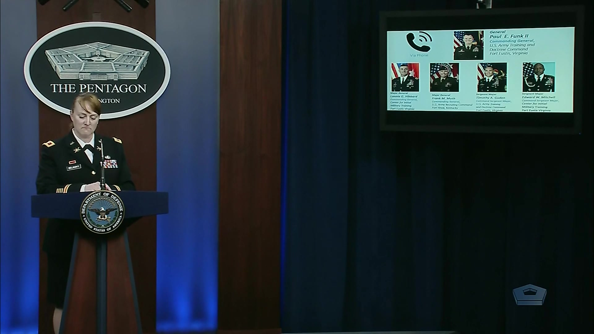 A service member stands at a lectern with a screen behind her.