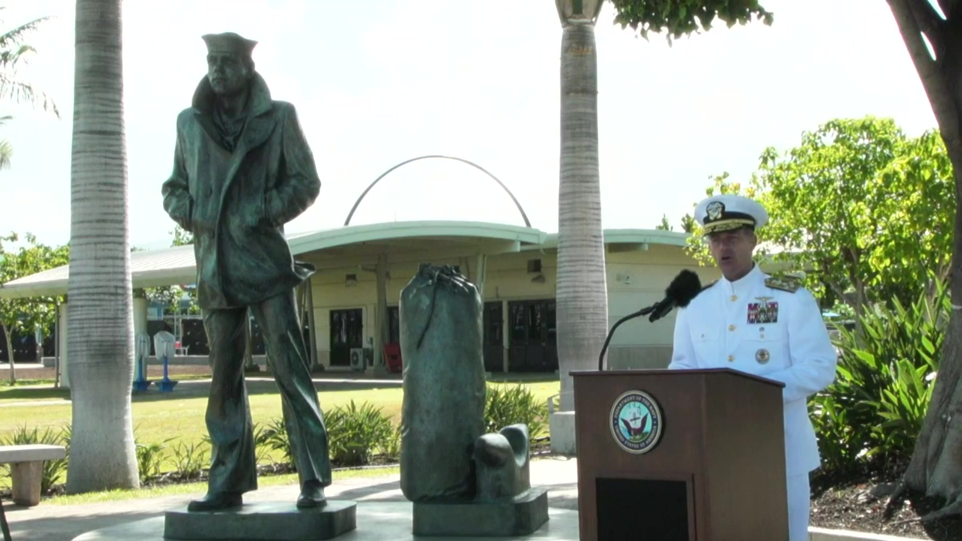 A sailor speaks at a lectern outside.
