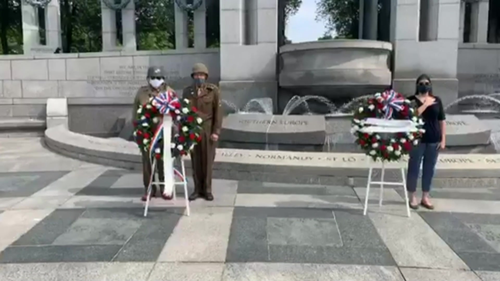 Three people, two in period military uniforms, stand by two wreaths at a memorial.