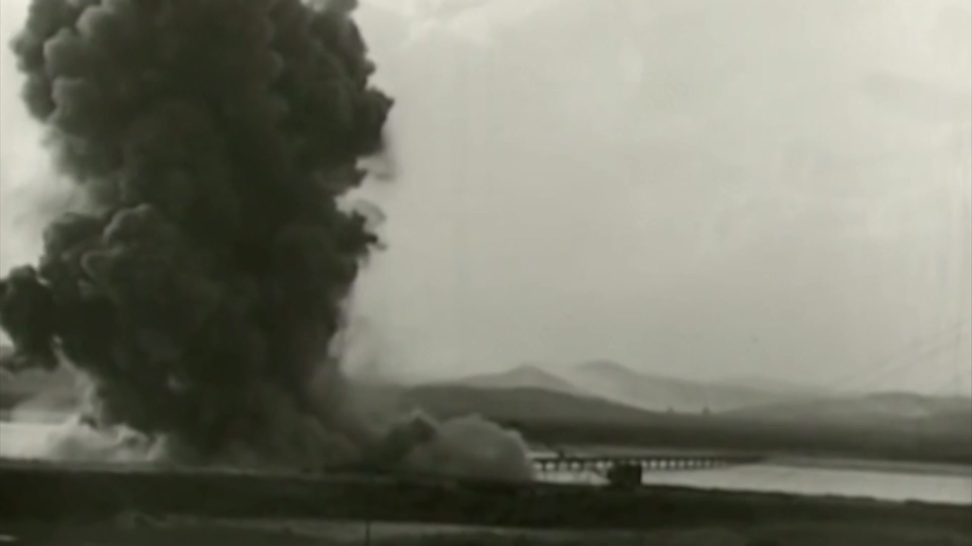 Black smoke billows up near a body of water, as if from an explosion.