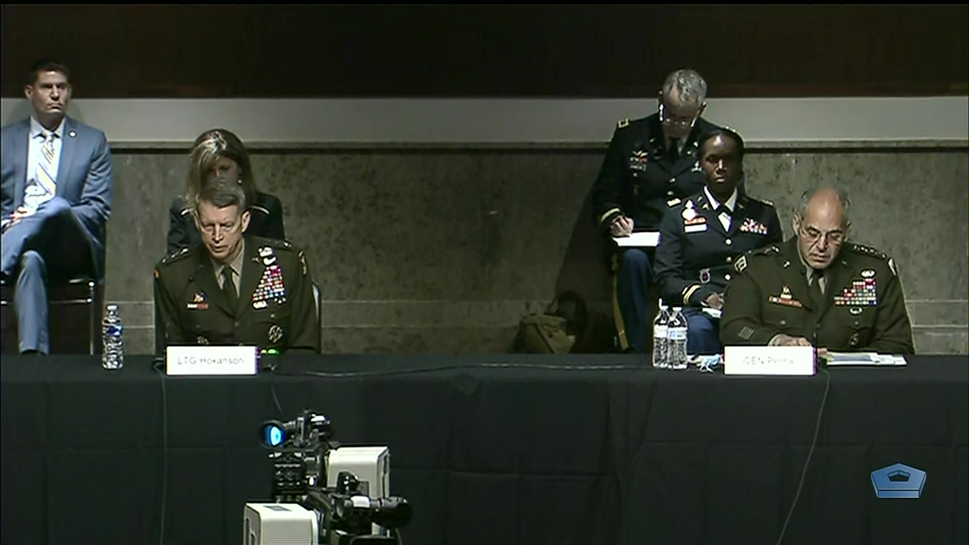 Service members sit at a table, with other troops and civilians behind them.