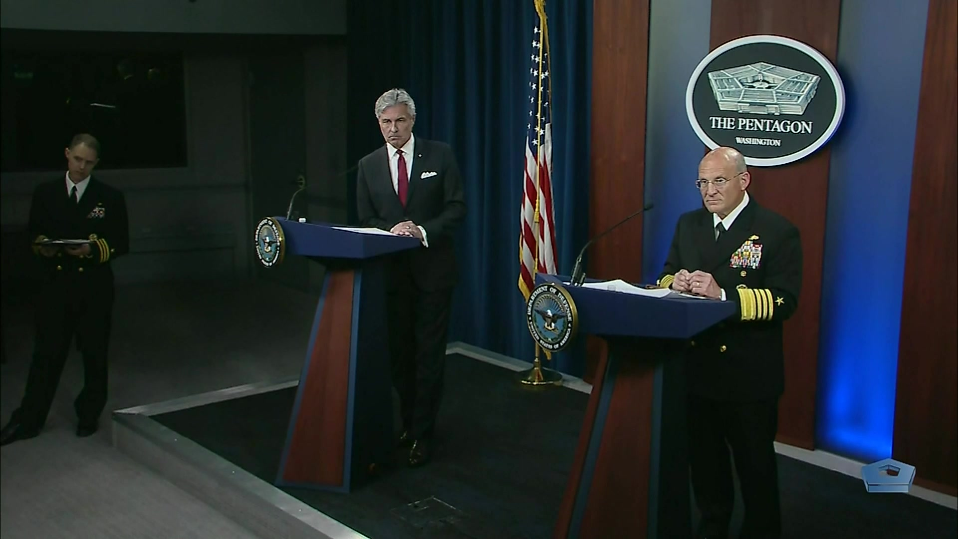 A civilian and a Navy admiral stand at lecterns.