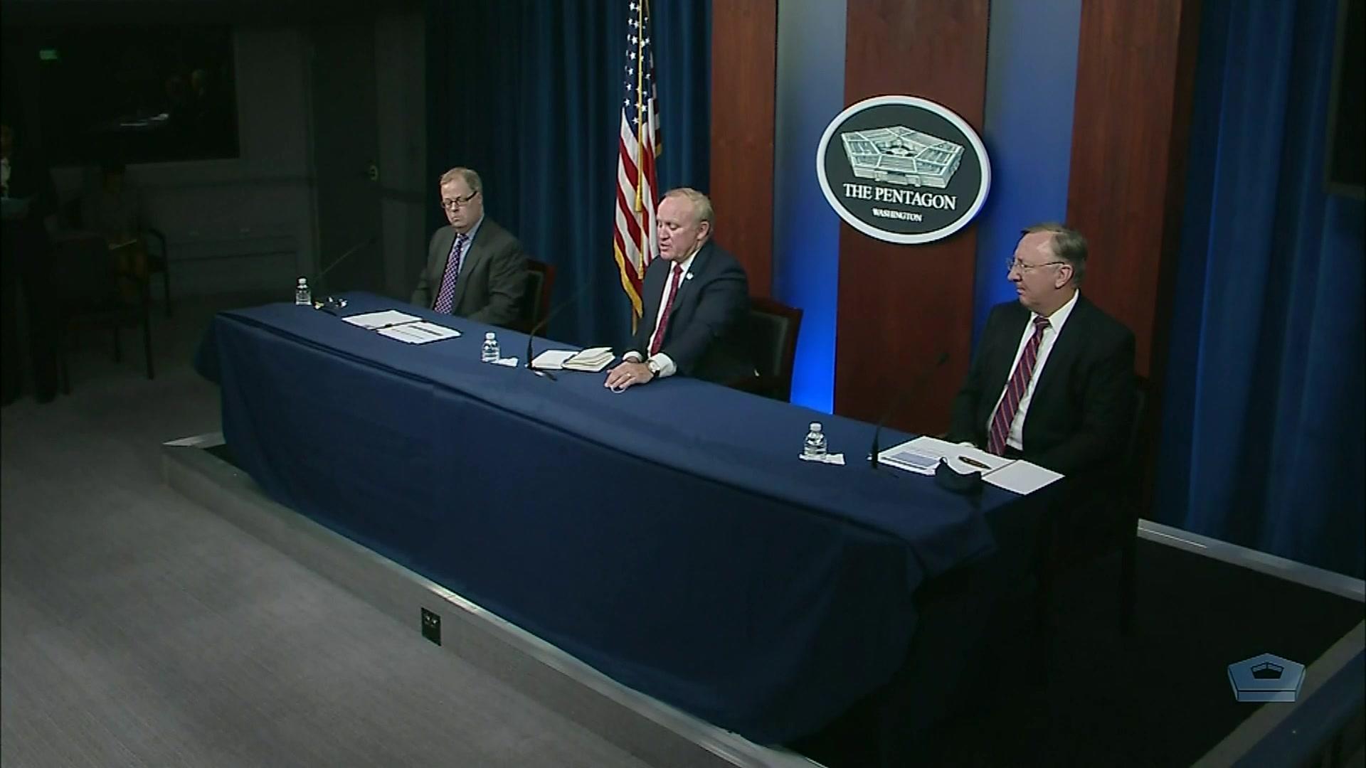 Three men sit at a table.
