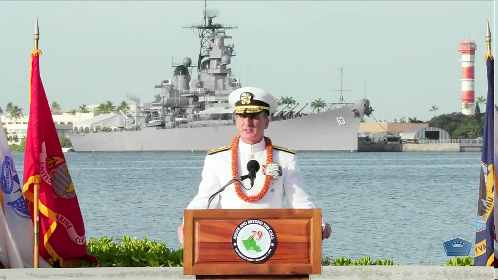 A sailor speaks at a lectern on a waterfront, with a ship moored in the background.