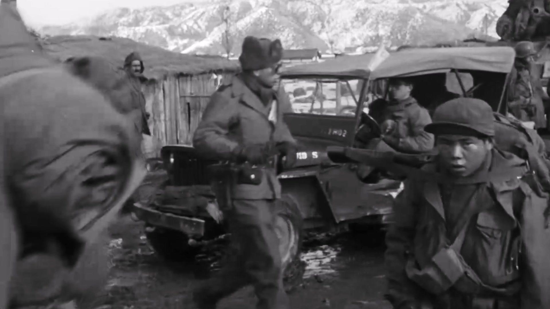 Troops gather outside in winter gear against a snowy mountain backdrop.
