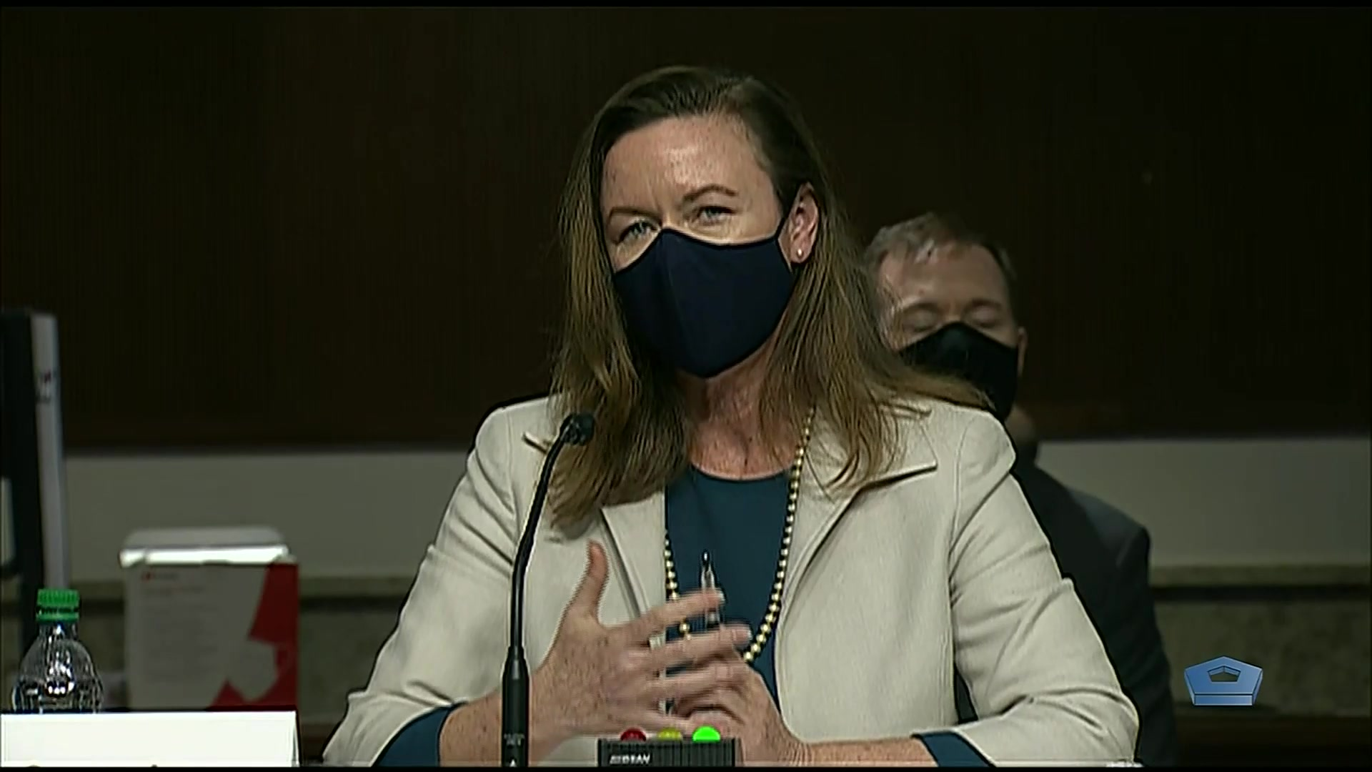 A civilian wearing a face mask sits and speaks.