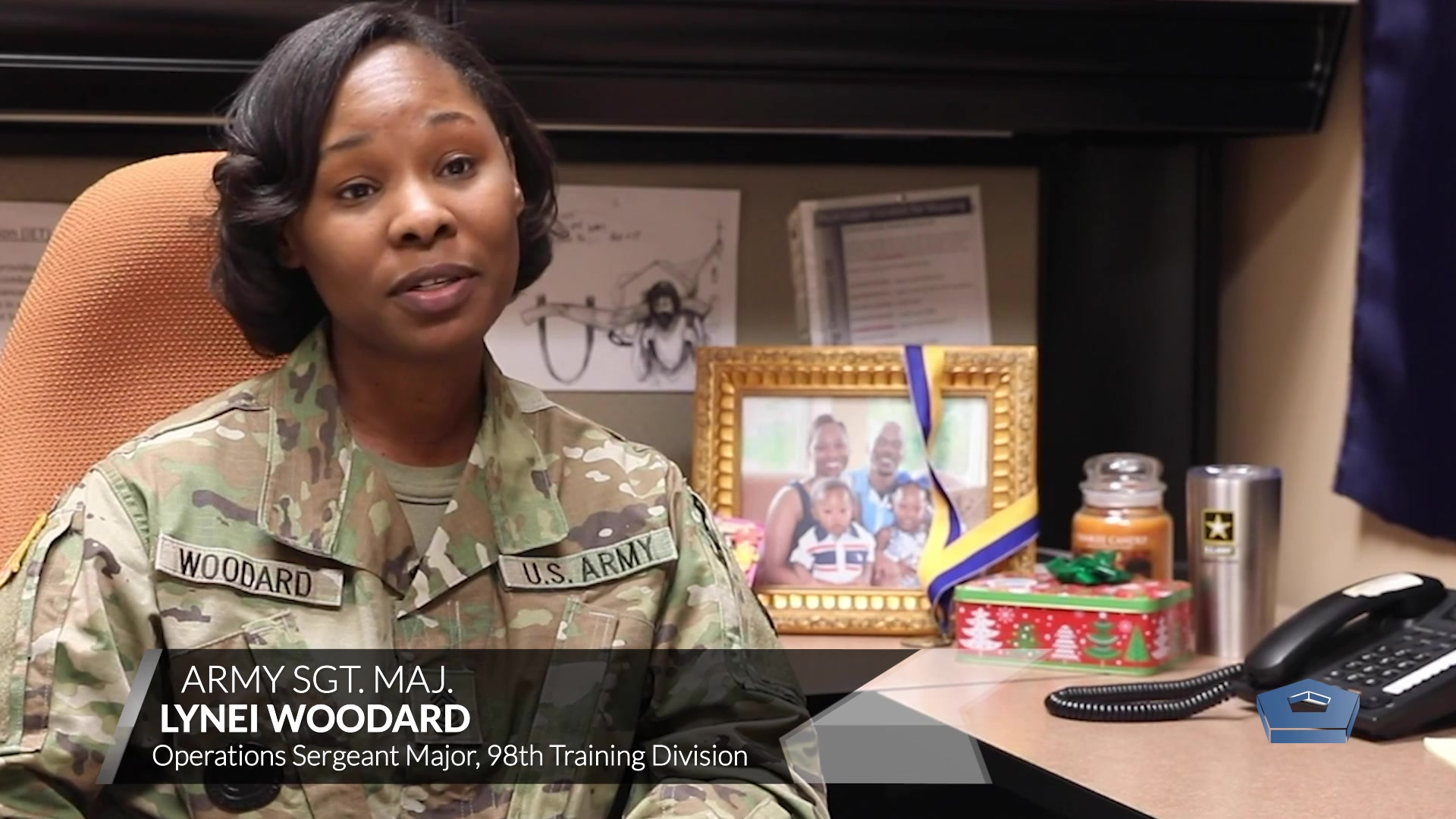 A soldier speaks while sitting at a desk.