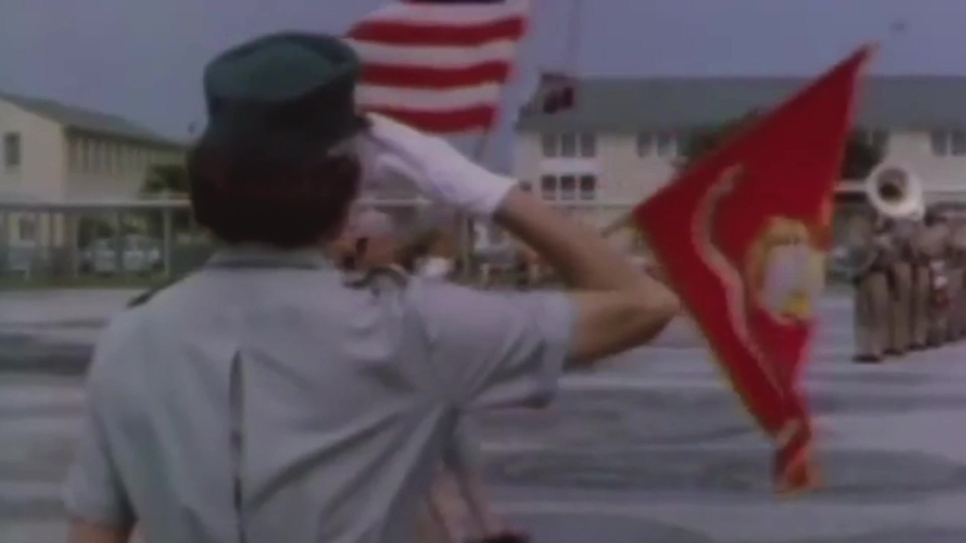 A Marine salutes at others standing in formation with flags.