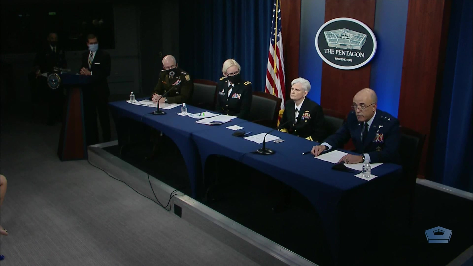 Service members sit at a table as a civilian stands at a lectern beside them.