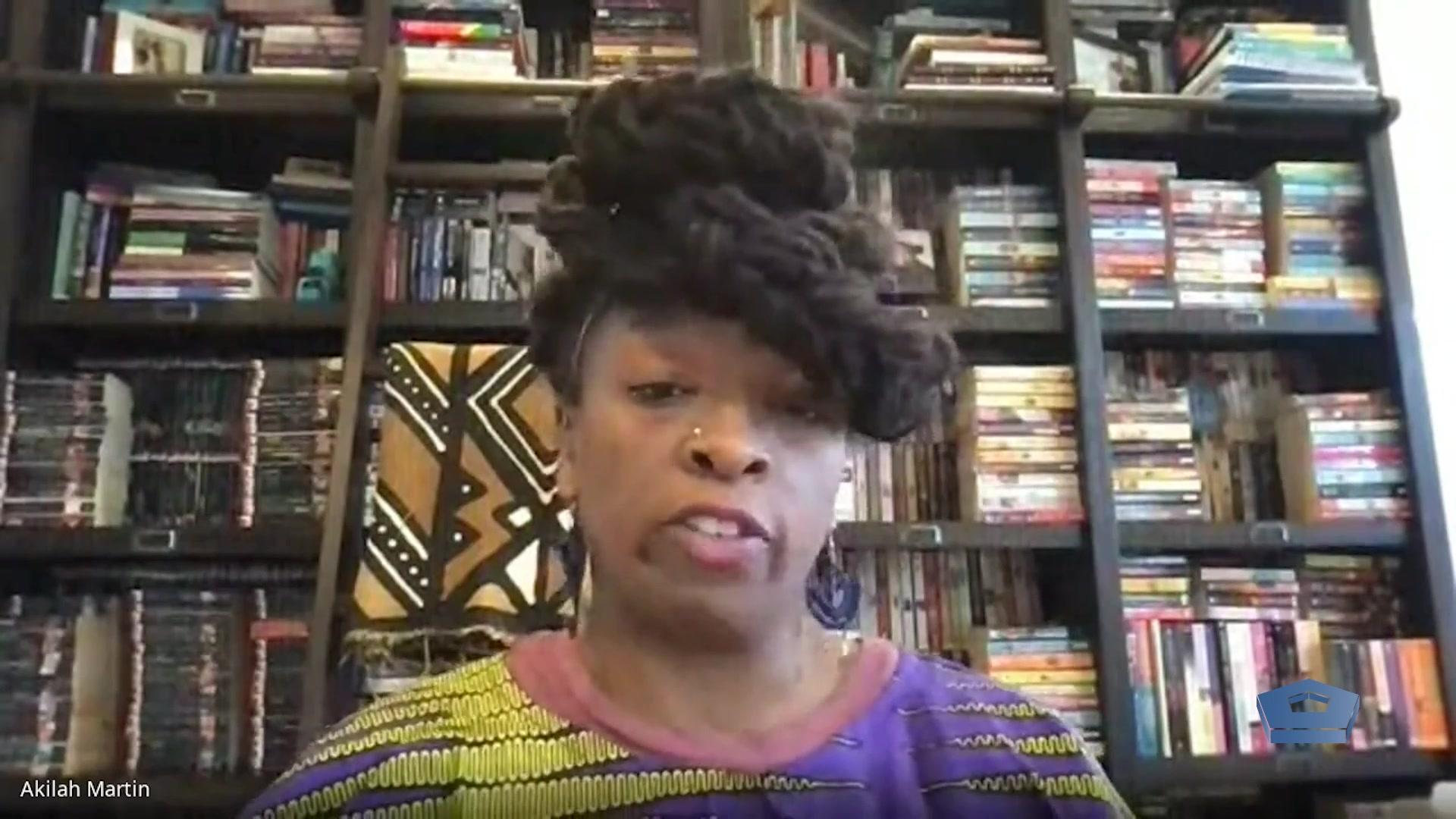 A civilian speaks in front of a bookshelf.