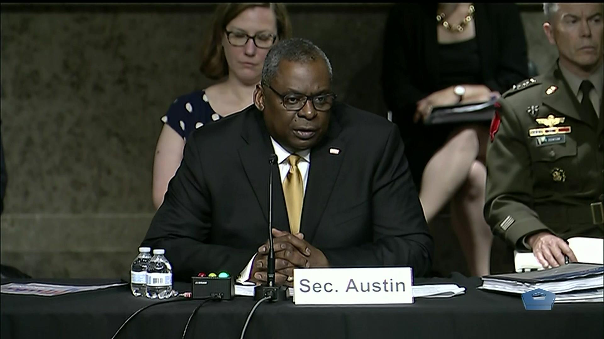 Secretary of Defense Lloyd J. Austin III sits and speaks at a table.