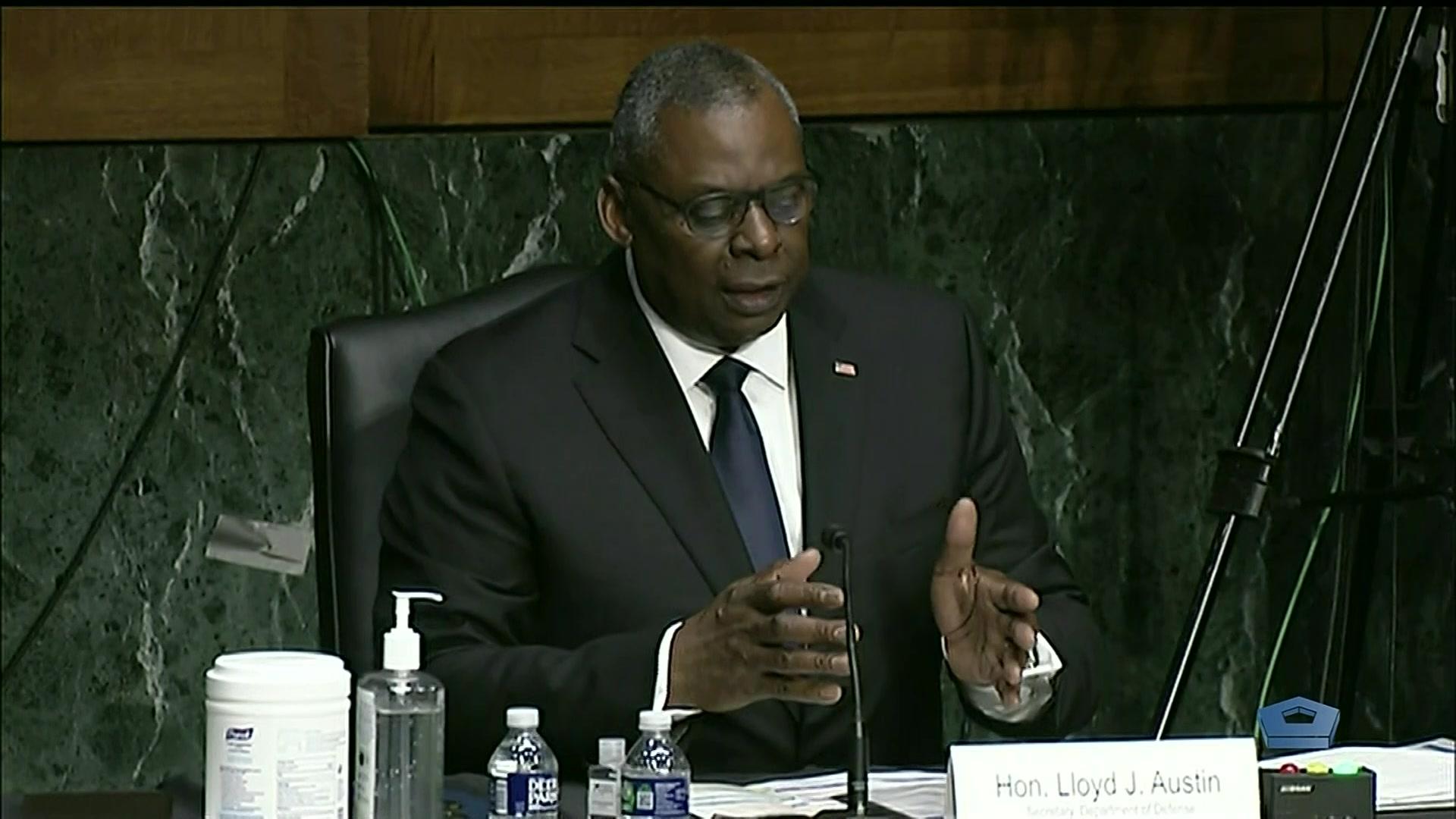 Secretary of Defense Lloyd J. Austin III speaks at a table.
