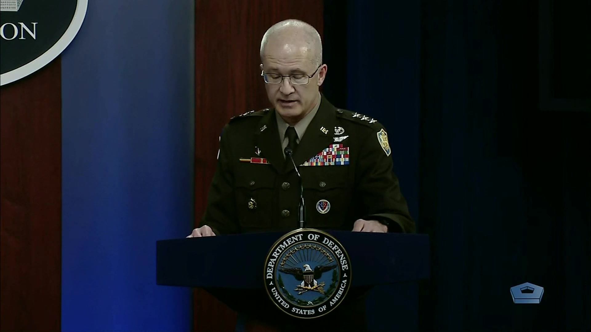 A military official speaks at a lectern.