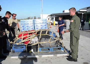 U.S. Coast Guard crew members from Air Station Clearwater, Florida and airmen from the 136th Airlift Wing, from the Texas Air National Guard, work together to deliver 22,000 lbs of water (about 15,000 bottles), supplies and personnel to Key West, Florida, Wednesday, Sept. 13, 2017. The supplies and personnel arrived aboard an HC-130 Hercules airplane from Air Station Clearwater to support Hurricane Irma relief operations. (U.S. Coast Guard video and photos by PA1 Zachary Crawford)