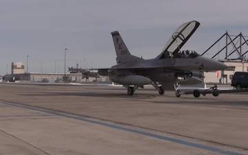Maintenance crews tow F-16 fighter jets in preparation for winter storm