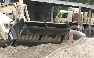 Missouri Guardsmen work with local civilians to sure up a levee.