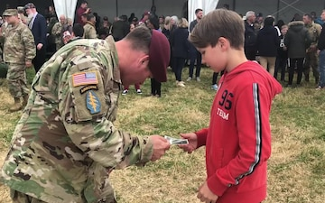 82nd Airborne Division Solider offers patch to French boy