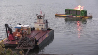 Floating barge with air curtain burner incinerates Lake Cumberland debris