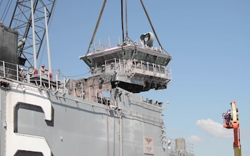 Salvage contractors remove pieces of USS Bonhomme Richard superstructure to ready the ship for towing