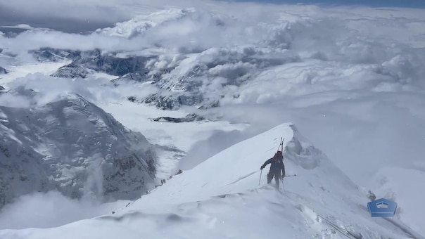 mountaineer scales steep rocks of denali